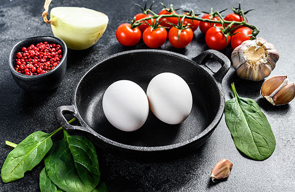 Ingredients Eggs, onion, garlic, tomatoes, pepper, spinach. Black background. Top view