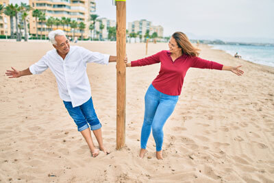 Middle age couple in love walking having fun at the beach happy and cheerful together