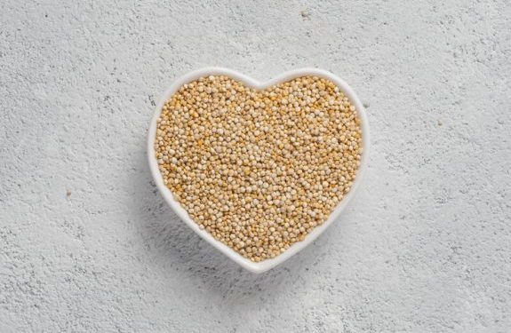 Quinoa in heart-shaped bowl on gray cement background.