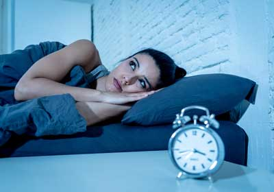 young beautiful hispanic woman at home bedroom lying in bed late at night trying to sleep suffering insomnia